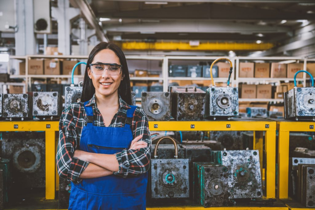 Portrait of smiling young technician woman in factory
