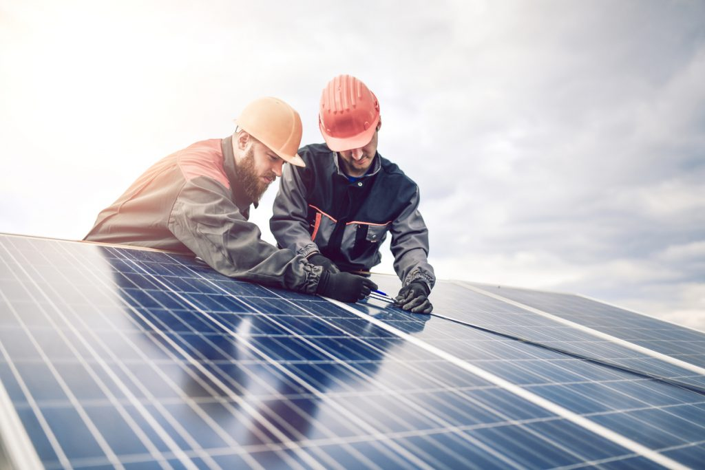 Workers Measuring Photovoltaic Cells Dimensions Of Solar Panel